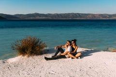 Kochający pary obsiadanie na krawędzi falezy morzem Ślubna podróż Miesiąc miodowy wycieczka Chłopiec i dziewczyna przy morzem obrazy stock
