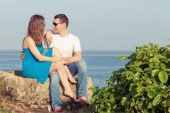 Kochający pary obsiadanie na plaży przy dnia czasem zdjęcie stock