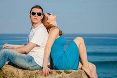 Kochający pary obsiadanie na plaży przy dnia czasem obrazy stock