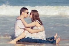 Kochający pary obsiadanie na plaży przy dnia czasem Obraz Stock