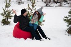 Kochający pary obsiadanie w parku w krześle bawić się snowballs fotografia royalty free