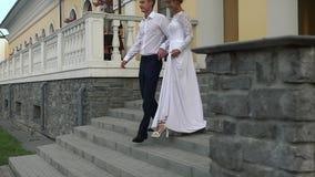 Kochający pary przybycie z restauracyjnych derzhast ręk, iść puszek schodki na ich dniu ślubu zdjęcie wideo