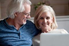 Kochający starszy mąż patrzeje uśmiechniętej dojrzałej żony używa lapto obrazy royalty free