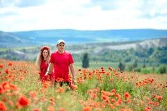 Kochaj?ca para ma zabaw? w polu z makowymi kwiatami fotografia royalty free