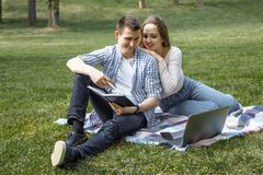 Kochający para ucznie robi pracie domowej w parku Obrazy Royalty Free