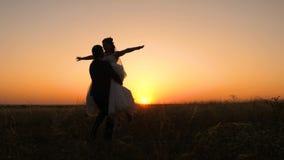 Kochanek panna młoda w bielu fornala i sukni tanu przy zmierzchem w lecie w polu młodzi para małżeńska buziaki wewnątrz, uściśnię zbiory wideo