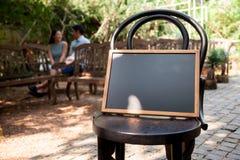 Kochanek siedzi szczęśliwie opowiadać Blackboard dla stawiać chrzcielnicy w przedpole zdjęcia royalty free