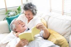 Kochankowie w żywym pokoju Szczęśliwa starsza para relaksuje wpólnie w domu z męża lying on the beach na podołku jego żona gdy cz zdjęcia stock