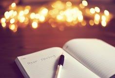 ` Kochany kochany ` napisał na białej książce podczas gdy siedzi w drewnianej zakładce obraz royalty free