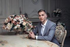 Kochany młody człowiek z ostrzyżeniem w kostiumu, siedzi przy stołem w pokoju z klasycznym wnętrzem luz Męski piękno zdjęcia stock
