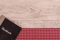 Kochbuch auf karierter Tischdecke Stockbilder