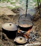 Kochen über einem Lagerfeuer Stockfotos