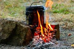 Kochen auf Lagerfeuer beim Kampieren stockfotografie