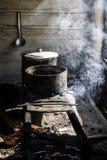 Kochen in den Kasserollen auf einem improvisierten Ofen über einem Feuer Lizenzfreies Stockfoto