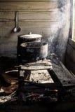 Kochen in den Kasserollen auf einem improvisierten Ofen über einem Feuer Lizenzfreie Stockfotos