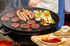 Kochen der Burger und der Würste auf Grill Stockfotografie