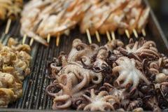 Kochen der Krake und anderer Meeresfrüchte auf einem Grill Lizenzfreies Stockfoto
