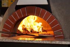 Kochen der Pizza in den traditionellen Holzofen Stockbilder