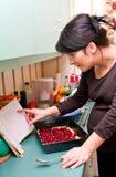 Kochen der schwangeren Frau Stockbild