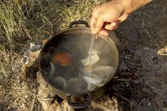 Kochen der Suppe über Lagerfeuer in der Wanderung Stockbilder