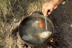 Kochen der Suppe über Lagerfeuer in der Wanderung Lizenzfreie Stockfotos