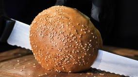 Kochen des Hamburgers Frauen ` s übergibt den Schnitt der Brötchen mit Samen des indischen Sesams auf den Teilen stock video
