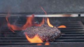Kochen des Hamburgers Rindfleisch- oder Schweinefleischkotelett, das auf Gitter grillt Kochen Sie den Mann, der ein Burgerpastetc stock video footage