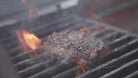 Kochen des Hamburgers Rindfleisch- oder Schweinefleischkotelett, das auf Gitter grillt Kochen Sie den Mann, der ein Burgerpastetc stock video