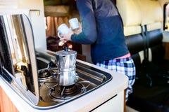Kochen des Kaffees in campervan, im Wohnwagen oder in RV auf Camping-Ausflug lizenzfreies stockfoto