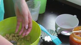 Kochen des Kuchens Frau knetet Teig in der Backform Sind in der Nähe Stau in einem Glas und andere Bestandteile stock footage