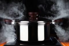 Kochen des Lebensmittels mit heißer Stromenergie des stanless Stahltopfes auf elektr. stockbilder