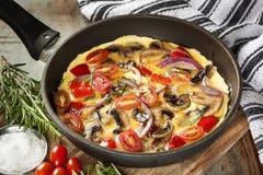 Kochen des Omeletts in der Bratpfanne Lizenzfreie Stockfotos