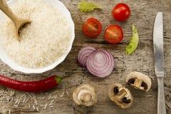 Kochen des Reises auf gealtertem hölzernem Hintergrund Schneiden Sie Zwiebel, Pilze Chile-Pfeffer, Kirschtomaten, grüner Salat Ge Lizenzfreie Stockfotos
