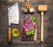 Kochen des Rindfleischsteaks, des hölzernen Hammers für Fleisch, des Fleischbeils, des Ölgewürzes und des Dills lizenzfreie stockfotos