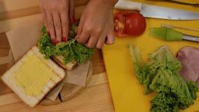 Kochen eines Sandwiches in der Küche Ansicht von oben genanntem, eine Hand nimmt ein grünes Blatt des Kopfsalates und setzt es au stock footage