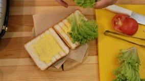 Kochen eines Sandwiches in der Küche Ansicht von oben genanntem, eine Hand nimmt ein grünes Blatt des Kopfsalates und setzt es au stock video