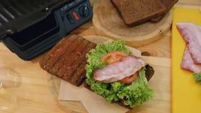 Kochen eines Sandwiches in der Küche Die Draufsicht der Hand mit den Zangen nimmt ein heißes gerade-geröstetes Stück Fleisch vom  stock footage