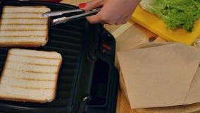 Kochen eines Sandwiches in der Küche Draufsicht der Hand mit Zangen nimmt weißes Toasttoastbrot vom Sandwichhersteller und -lage stock video footage