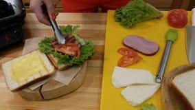 Kochen eines Sandwiches in der Küche Eine weibliche Hand mit Zangen nimmt eine frische geschnittene Tomate und legt sie auf Brot  stock video footage