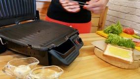 Kochen eines Sandwiches in der Küche Seitenansicht der Hand mit den Zangen nimmt ein heißes gerade-geröstetes Stück Fleisch vom G stock footage