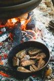 Kochen im Freien in einer Schüssel Edelstahl über einem brennenden Feuer Stockfotografie