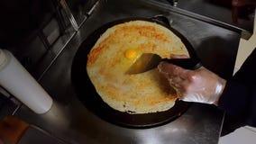 Kochen Sie das Knacken eines Eies auf Krepp auf einem schwarzen Kocher stock footage