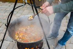 Kochen Sie das Rühren der Suppe in einem großen Kessel stockfotos