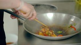 Kochen Sie gebratene Garnelen mit Gemüse in einer Bratpfanne, wässerte sie mit Soße stock video footage