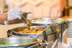 Kochen Sie oder der Chef, der ein Buffet am Restaurant füllt lizenzfreies stockbild