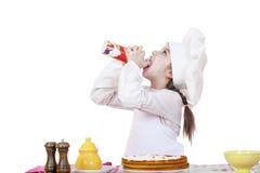 Kochen und Leutekonzept - lächelndes kleines Mädchen im Kochhut Stockfotografie