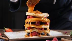 Kochen von Kunst Ausgebreitetes Karamell des Chefs auf Stapel frische flaumige Pfannkuchen verziert mit Waldbeeren selbstgemacht stock video