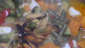 Kochen von Meeresfrüchten mit Gemüse im Eisentopf stock video