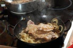 Kochen von Rindfleischsteaks und von gebratenen Zwiebeln Stockfotos