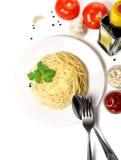 Kochen von Spaghettis auf einer Platte mit Gemüse auf einem weißen Hintergrund Stockbild